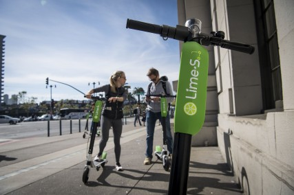People use a smartphone to unlock Neutron Holdings Inc. LimeBike shared electric scooters on the Embarcadero in San Francisco, California, U.S., on Thursday, May 3, 2018. City officials, eager to do something about the electric scooters issue, are sending cease-and-desist letters and are planning to require permits soon, while impounding any that they say are parked illegally. Photographer: David Paul Morris/Bloomberg via Getty Images